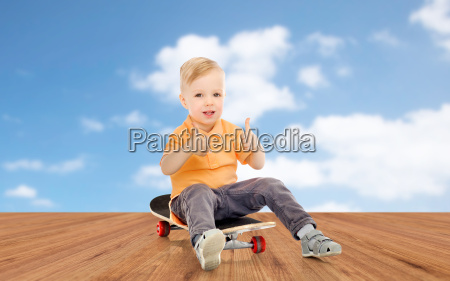 happy little boy on skateboard showing