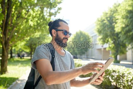 mann unterwegs mit rucksack und tablet