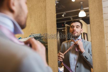 man tying tie on at mirror
