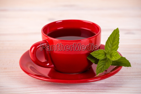 red cup of tea with green