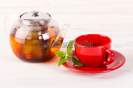 teapot and red cup on wooden