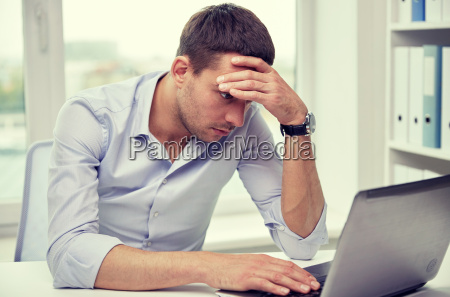 betonter geschaeftsmann mit laptop im buero