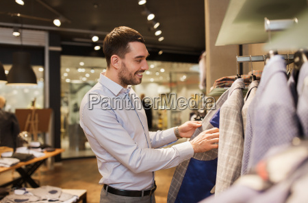 happy young man choosing clothes in
