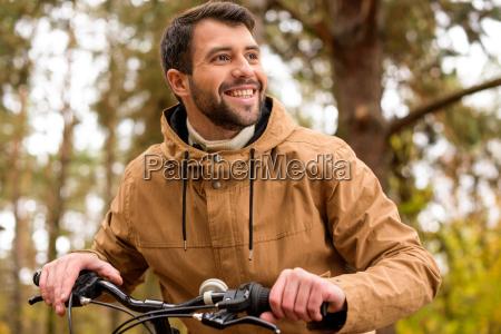 laechelnder mann sitzt auf dem fahrrad