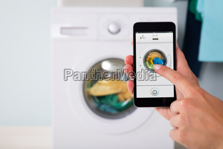person operating washing machine using cellphone