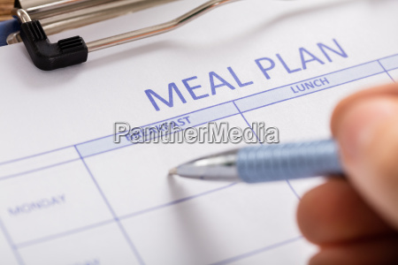 person hand filling meal plan form