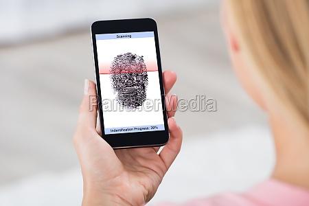 person mit handy angezeigt fingerabdruck scanner