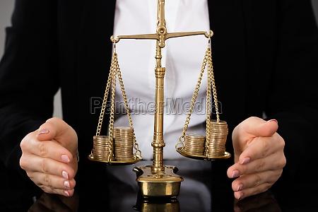 rechtsanwaeltin die gerechtigkeitskala mit muenzen schuetzt