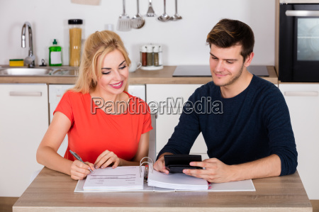 happy couple calculating invoice in kitchen
