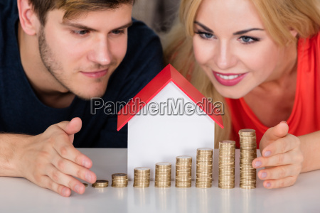 couple protecting house model with stacked