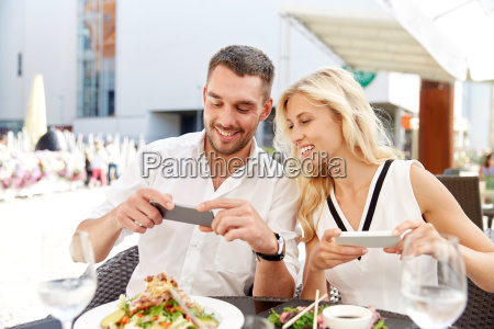 happy couple with smatphone photographing food