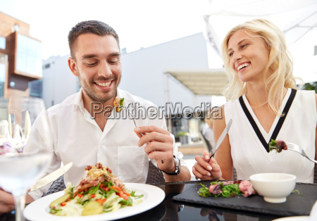 happy couple eating dinner at restaurant