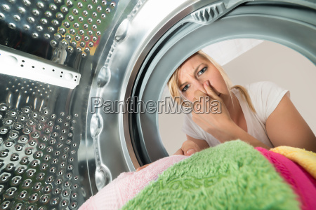 woman inserting stinking clothes in washing