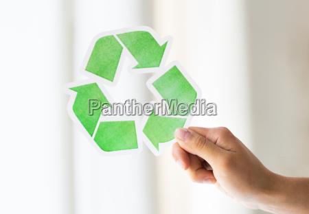 nahaufnahme von hand mit gruenen recycling