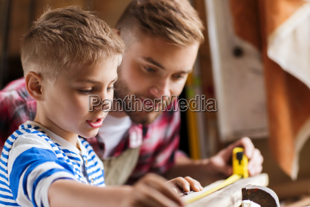father and son with ruler measure