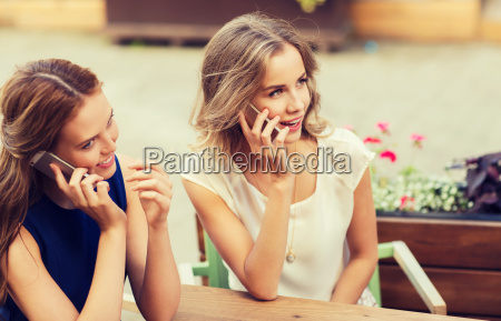 happy young women with smartphones at