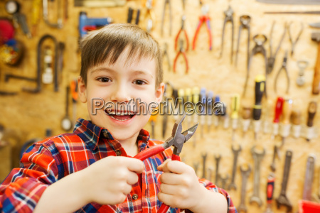 happy little boy with pliers at