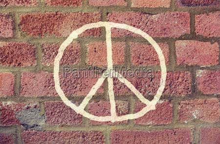 friedenszeichen auf roten backsteinmauer zeichnen