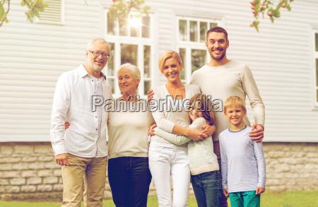 glueckliche familie vor dem haus im