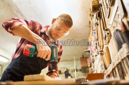 tischler mit bohrplank in werkstatt