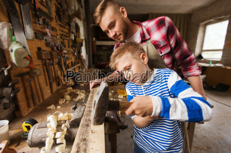 father and son with hammer working