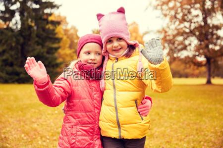 zwei glueckliche kleine maedchen winken hand