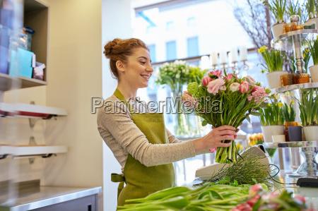 laechelnd floristin frau die buendel in