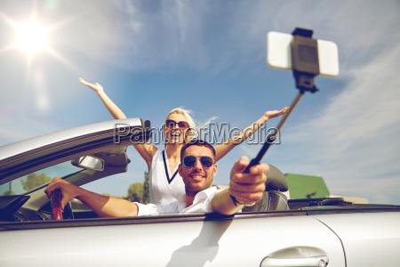 happy couple in car taking selfie