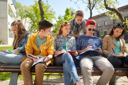 schuelergruppe mit notizbuechern auf schulhof