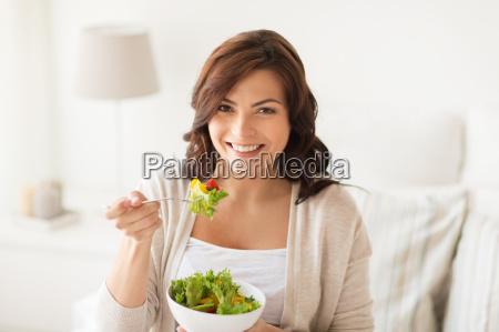 laechelnde junge frau zu hause salat