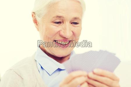 glueckliche seniorin spielt karten zu hause