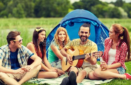 glueckliche freunde mit getraenken und gitarre
