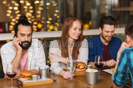 mann mit smartphone und freunden im