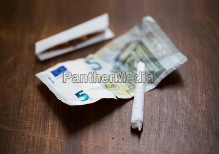 nahaufnahme von marihuana joint und geld