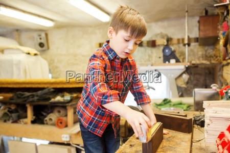 gluecklicher kleiner junge mit planke und