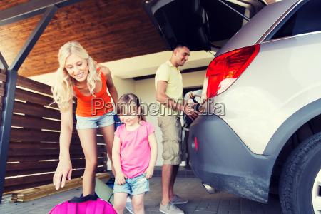 glueckliche familie verpackung dinge zu auto