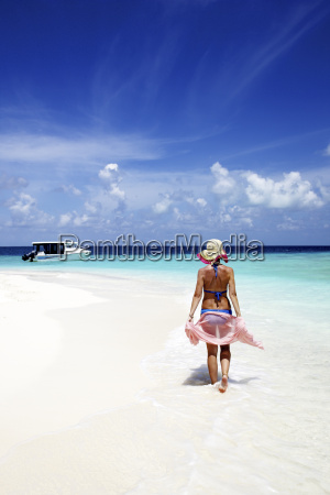maldives woman walking on sand beach