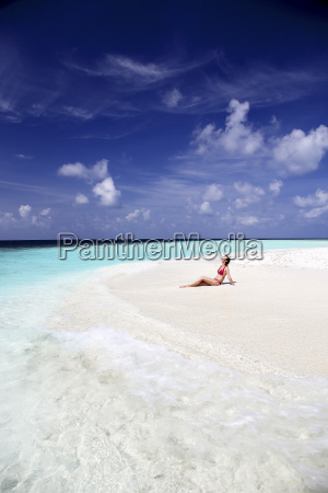 maldives woman sitting on beach at