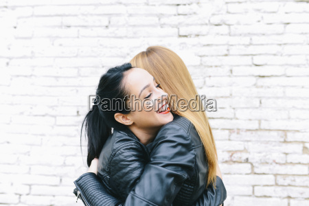 two young women hugging in front