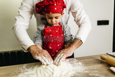 father and son kneading dough together