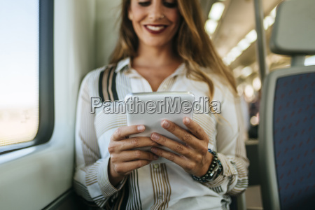 smiling woman on a train using