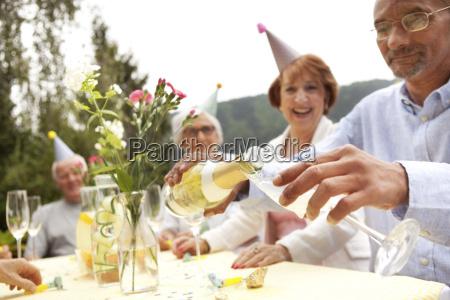 senior people celebrating man pouring champagne