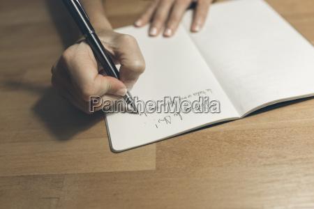 frau schreibt in notizbuch mit einem