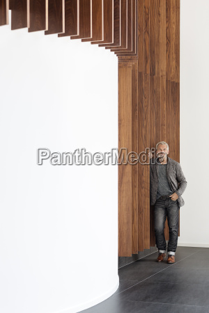businessman standing at wooden wall looking