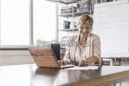 smiling businesswoman with cell phone and