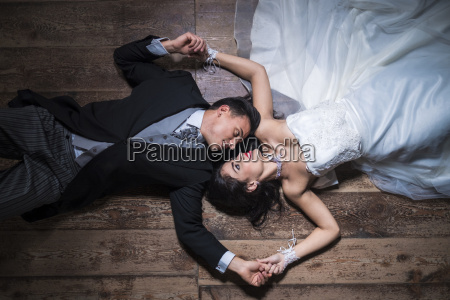 bridal couple lying on wooden floor