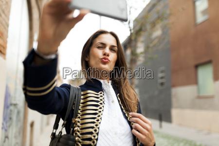 modische junge frau nimmt ein selfie