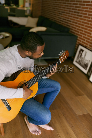 junger mann zu hause spielt gitarre