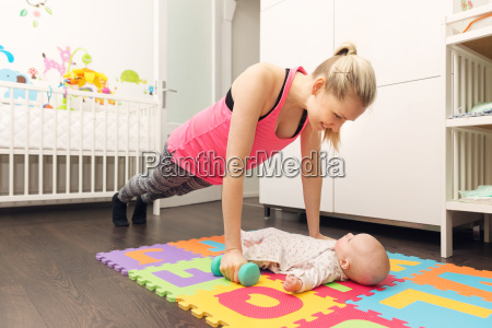 mother doing fitness and playing with