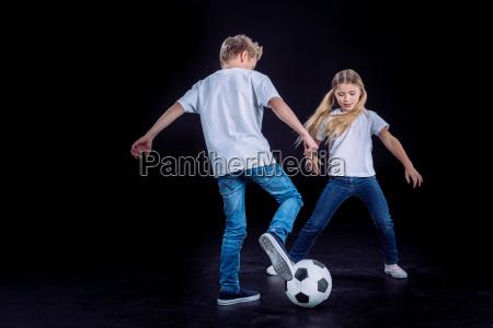 bruder und schwester mit fussball spielen